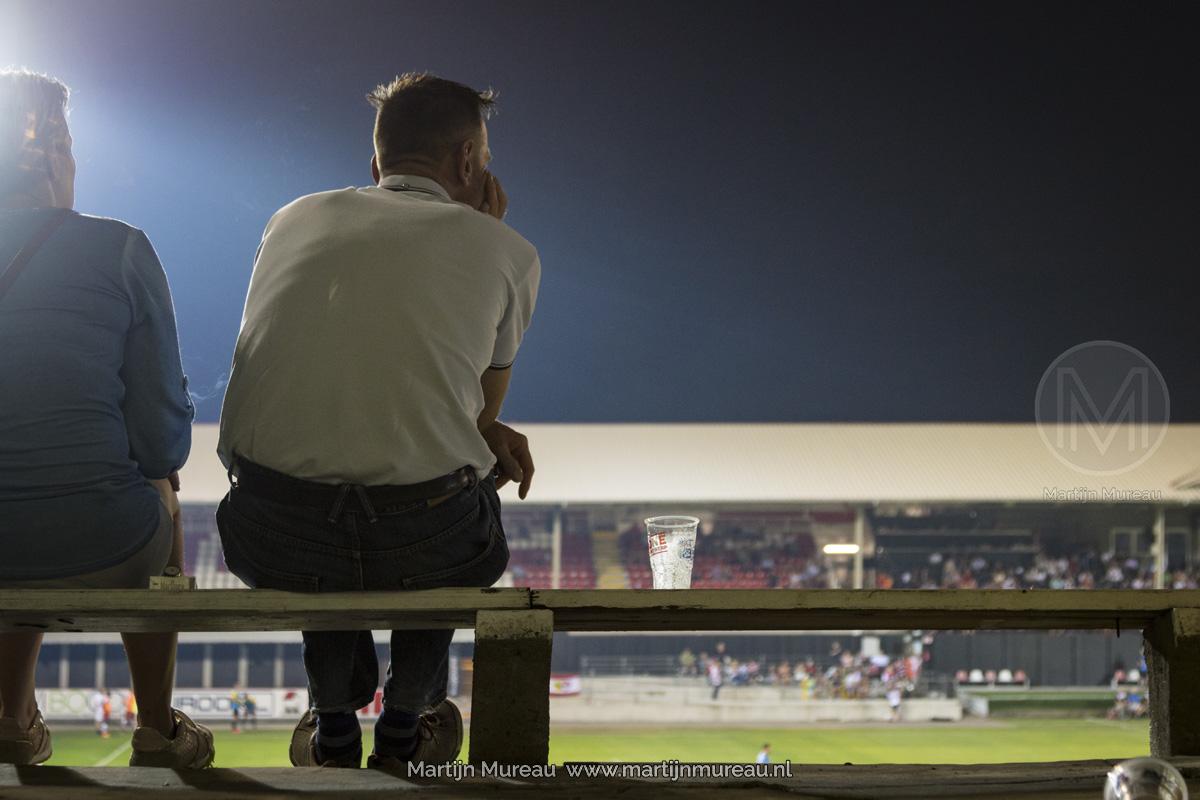 Een fan van Royal Antwerp FC kijkt -met zijn biertje naast zich- aandachtig naar de wedstrijd